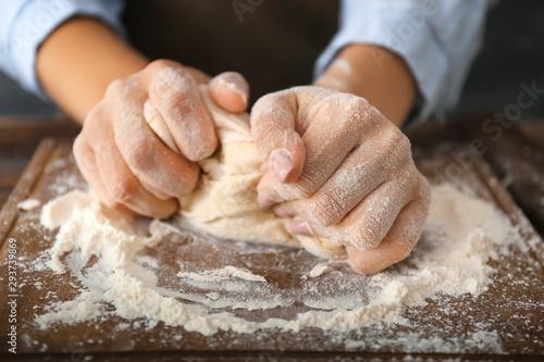 Spoed Fotobehang Bakkerij Woman kneading flour in kitchen, closeup