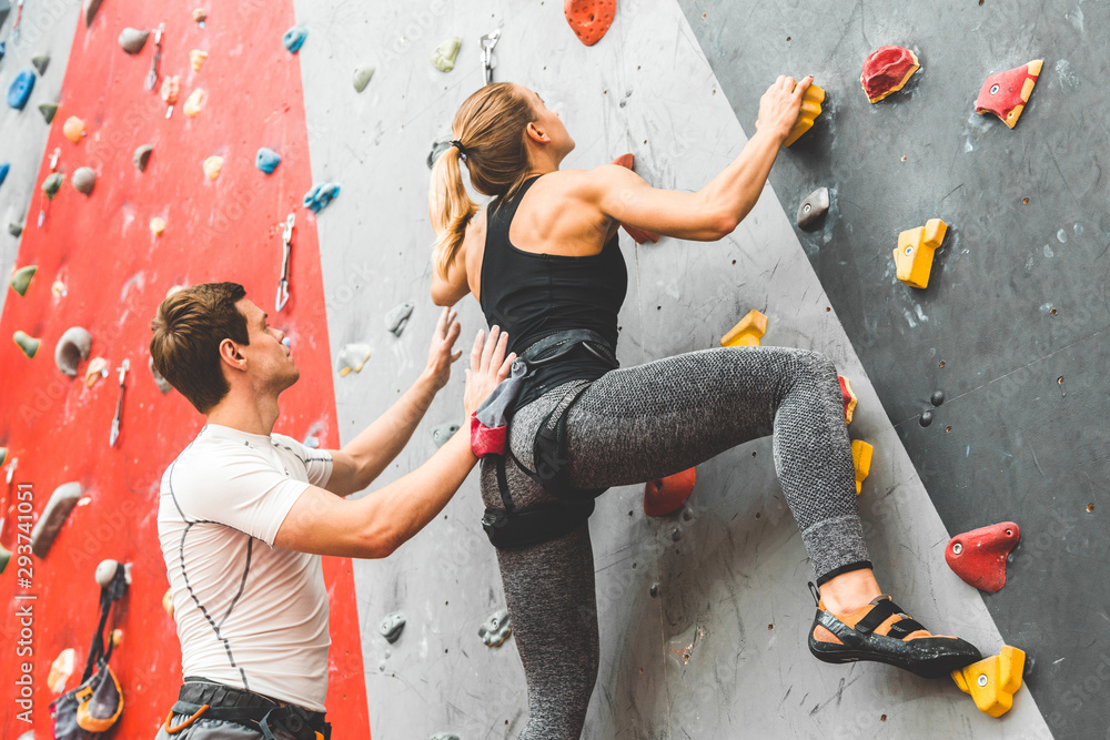 Fototapety, obrazy: couple of athletes climber moving up on steep rock, climbing on artificial wall indoors. Extreme sports and bouldering concept