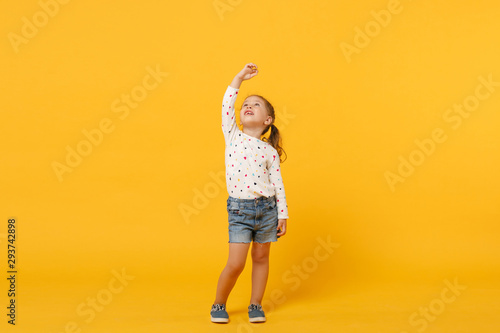 Little cute child kid baby girl 4-5 years old wearing light denim clothes isolated on pastel yellow wall background, children studio portrait. Mother's Day, love family, parenthood childhood concept. - 293742898