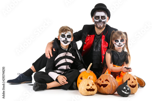 Foto Father with children in Halloween costumes and with pumpkins on white background