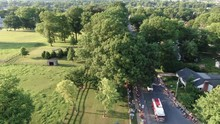Aerial Dolly Shot Of Firetruck In 4th Of July Parade In Small Town During Magic Hour, Crowds Watch And Wave