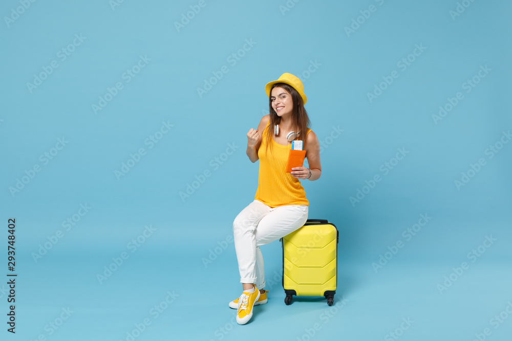 Fototapety, obrazy: Traveler tourist woman in yellow summer casual clothes hat hold tickets luggage isolated on blue background. Female passenger traveling abroad to travel on weekends getaway. Air flight journey concept
