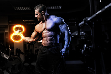 Fototapeta na wymiar Muscular athletic bodybuilder fitness model training arms with dumbbells on fire in gym. Concept sport photo of exercises in gym
