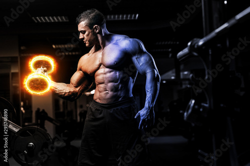 Pinturas sobre lienzo  Muscular athletic bodybuilder fitness model training arms with dumbbells on fire in gym