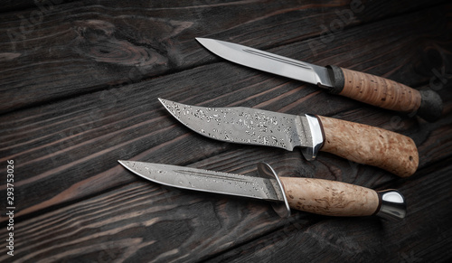 Hunting bowie knife with a wooden handle on dark wooden background Tableau sur Toile