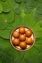 Indian Festival Dussehra, Symbolic Golden Or Piliostigma Leaf Or Bauhinia Racemosa Also Known As Apta Patti, Arranged In Circular Pattern With Gulab Jamun Sweet In Plate At Centre, Selective Focus