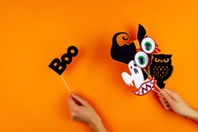 Female Hands Are Holding Paper Photo Props On Orange Background. Scary Ghost, Owl, Vampire Smile, Teeth, Blood Eyes, Witch Hat On Canvas. Party Carnival, Accessories For Celebrating Happy Halloween.