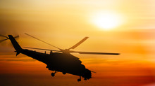 Helicopter Silhouette Flying In The Sky At Sunset