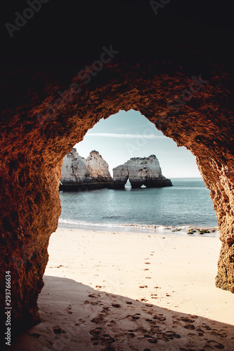Aluminium Prints Cathedral Cove Morning empty beach view with shadow of the beautiful wild rough rocks on the sand. Praia dos Três Irmãos, Prainha in Portimão, Algarve coast in Portugal, Atlantic Ocean