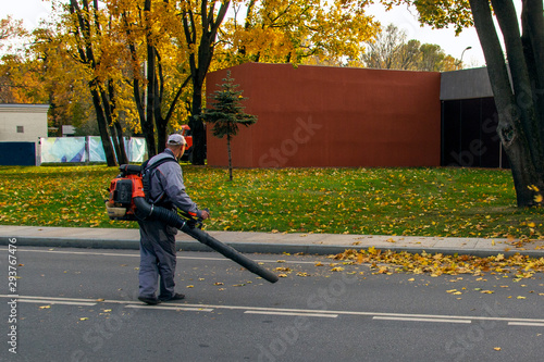 Photo Landscaper worker cleaning footway in a park from fallen leaves using a gas-powe