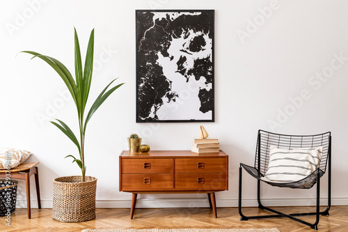 Stylish interior design of living room with wooden retro commode, chair, tropical plant in rattan pot, basket and elegant personal accessories. Mock up poster frame on the wall. Template. Home decor. - 293769407