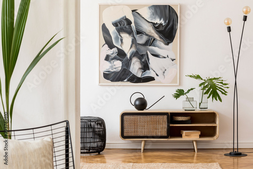 Fototapeta Scandinavian and design home interior of living room with wooden commode, design black lamp, rattan basket, plants and elegant accessories. Stylish home decor. Template. Mock up poster paintings.  obraz