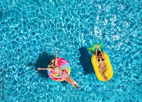 Glückliches Paar auf bunten Luftmatratzen treibt über blaues Pool Wasser Tapéta, Fotótapéta