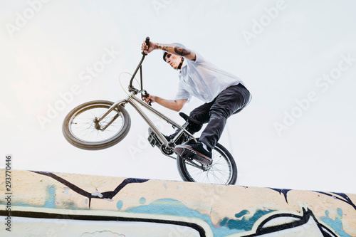 Side view of man riding and balancing while performing trick on BMX in skatepark.
