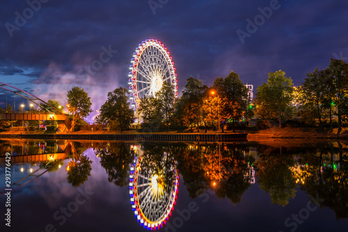 Germany, Colorful illuminated ferris wheel and lights of giant swabian fair called cannstatter wasen in stuttgart city by night reflecting in neckar river water
