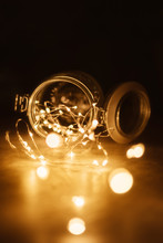 Fairy Light In Vintage Hipster Glass Jar With Blur Bokeh Dark Background.