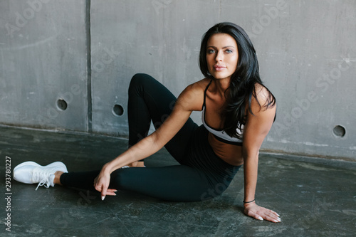 Fotomural young brunette fitness woman sitting on floor in brutal concrete gym