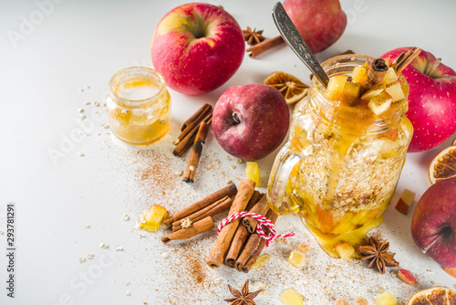 obraz lub plakat Autumn healthy breakfast idea. Overnight oatmeal in a mason jar with spiced honey apple, spices and candied orange. On a light concrete stone background,
