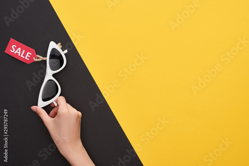 cropped view of woman holding glasses with sale label on yellow and black background