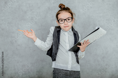 Fotografia Little girl with a folder in her hands on a gray background