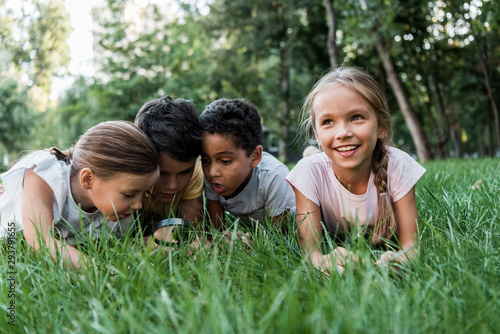 Obraz selective focus of cute multicultural children looking at green grass though magnifier - fototapety do salonu