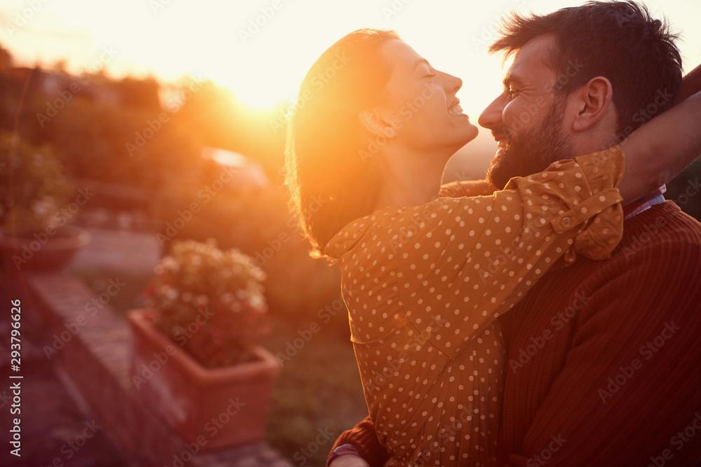 Fototapeta Smiling couple hugging and kissing at sunset.