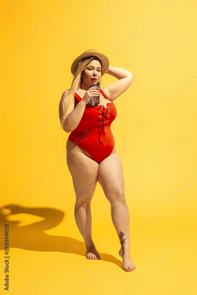 Fototapety, obrazy: Young caucasian plus size female model's preparing for beach resort on yellow background. Woman in red swimsuit and hat drinking cocktail. Concept of summertime, party, body positive, equality.