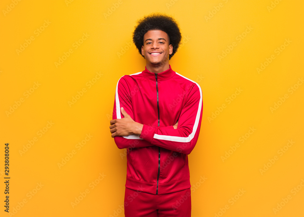 Fototapeta Young sport black man over an orange wall crossing arms, smiling and relaxed