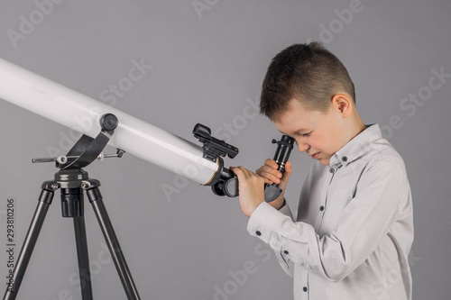 Photo young astronomer looks through a telescope and writes in the tablet