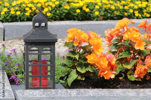 Photo  Grablaterne auf einem Friedhof, im leicht unscharfen Hintergrund zwei mit Sommer