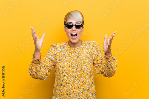 Vászonkép  Young curvy woman wearing a floral summer clothes receiving a pleasant surprise, excited and raising hands