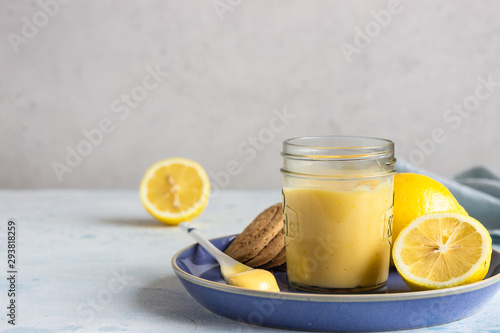 Fotografiet A jar of lemon curd or custard with a spoon and cookies on a blue plate and fresh lemon
