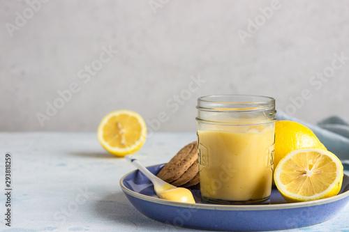 Obraz na plátně A jar of lemon curd or custard with a spoon and cookies on a blue plate and fresh lemon