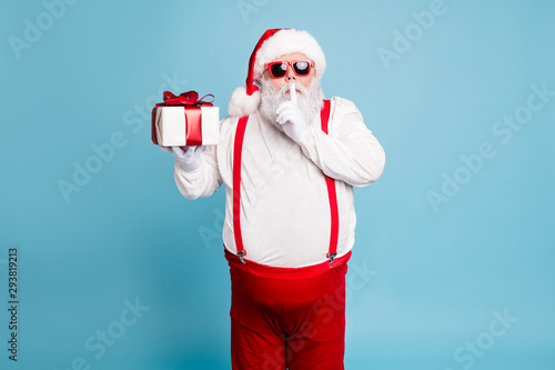 Fototapeta Hush its secret. Portrait of focused funny funky fat santa claus with big abdomen belly prepare gift for eve noel hold small giftbox wear red pants suspenders isolated over blue color background obraz