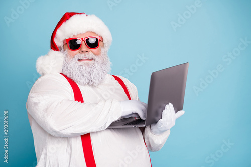 Close up photo of funny funky overweight santa claus in hipster sunglass use laptop search christmas season discounts type congratulations wear style suspenders isolated over blue color background