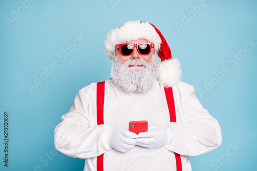 Close up photo of funny funky fat white grey-haired santa claus use cell phone type sms congratulations with noel in blogs wear overalls red suspenders sunglass isolated over blue color background