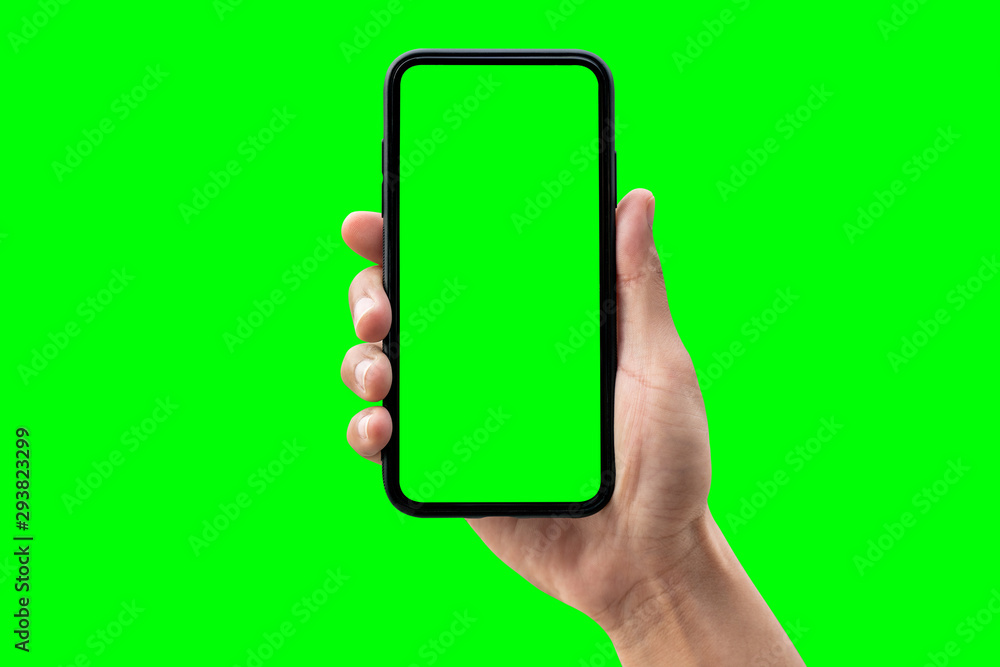 Fototapety, obrazy: Hand holding smartphone isolated on green background.