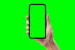 canvas print picture - Hand holding smartphone isolated on green background.