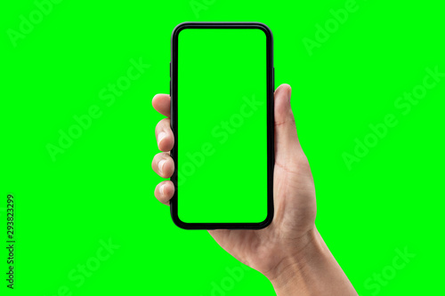 Hand holding smartphone isolated on green background. - 293823299