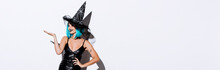 Panoramic Shot Of Happy Girl In Black Witch Halloween Costume With Blue Hair Pointing With Hand On White Background