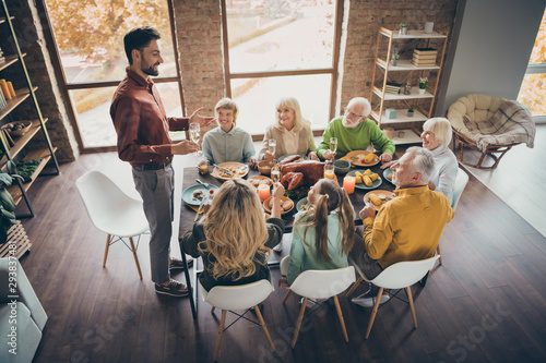Photo of full big family gathering sit feast meals dinner table father guy tell Fototapet