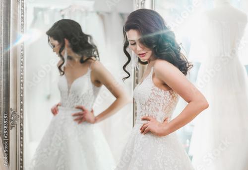 Leinwand Poster Beautifu bride choosing wedding dress in a wedding salon
