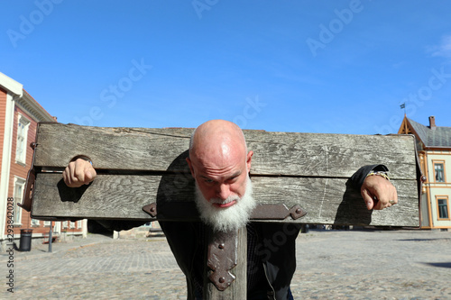 Bearded, bald man in a pillory, Old Town, Fredrikstad, Norway Wallpaper Mural