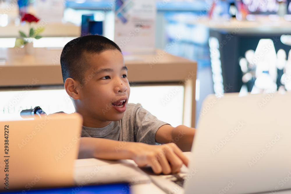 Fototapety, obrazy: Disabled child on wheelchair trying to use a computer with excitement in an IT shop , Special children's lifestyle, Life in the education age of special need kids, Happy disability kid concept.