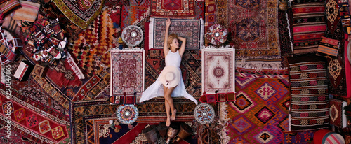 Carta da parati Beautiful happy girl in a long white dress laying on the carpet and rugs in Goreme, Cappadocia, Turkey