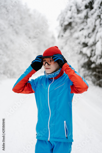 Teen sportsman putting on goggles in winter forest