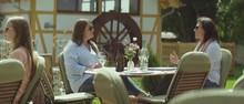 Two Women Sitting Outside In D...
