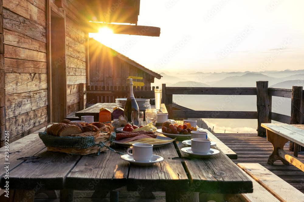Obraz Breakfast table in rustic wooden terace patio of a hut hutte in Tirol alm at sunrise fototapeta, plakat