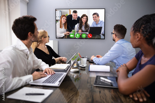 Businesspeople Discussing Graphs Through Videochat - 293897064