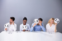 Sad Business People Showing Low Score Cards